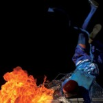 An acrobatic blue devil breathes fire. Photographer: Edison Boodoosingh