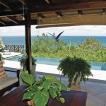 A patio with a view of the infinity pool and the Caribbean Sea at the Villas at Stonehaven, Tobago