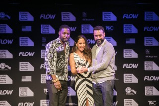 L-R: Fofi George, Community Relations Officer, NGC presents the Award for Best feature film to Kisha Tikina Burgos (screen writer) and Arí Manuel Cruz (director)