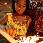 A little girl lights a starlight from a deya at Divali. Photo by Stephen Broadbridge