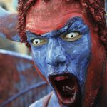 A menacing blue devil intimidates the crowd. Photo by Atiba Williams