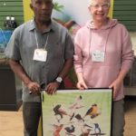 Winner of a giveaway by the Tobago Tourism Agency, festival attendee Carrie Cumming (right) is presented with her prize by Newton George