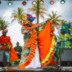 A cultural performer dances at a seaside festival in Tobago